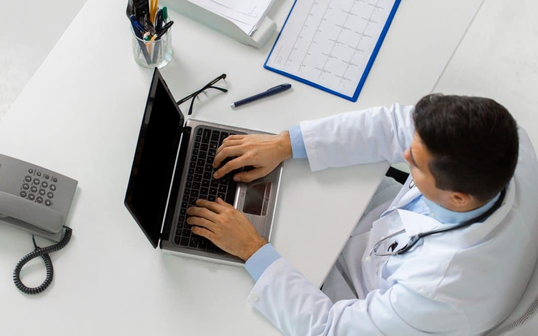 doctor with cardiogram and laptop at clinic
